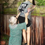 FY13BJ Mother helping daughter in climbing wooden fence at back yard. Image shot 2016. Exact date unknown.